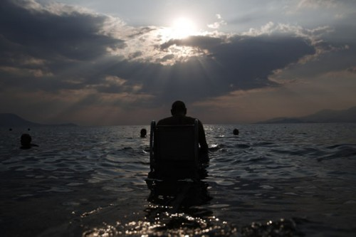 """Theofilou, who suffers from paraplegia, enters the sea with the aid of the """"Seatrac"""" device at a beach in Alepochori"""