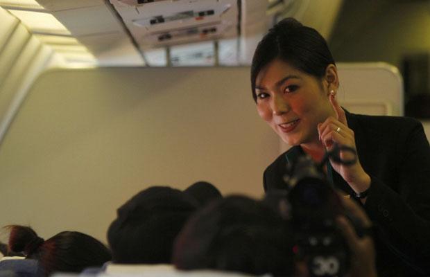 Nathatai Sukkaset, de 26 anos, conversa com passageiros durante o voo (Foto: Reuters)